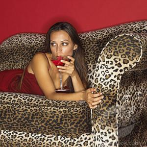 Woman Enjoying Mixed Drink on Plush Spotted Sofa